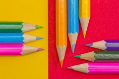 Coloring pencils on red and yellow background stock photography