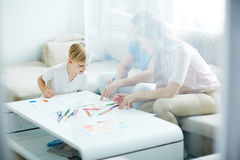 Coloring pictures. Young couple and little boy spending leisure by coloring pictures Stock Photo
