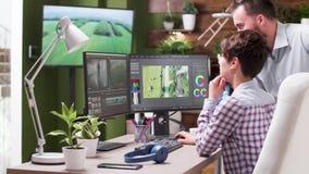 Colorist en hogere videoredacteur die over sommige projecten spreken stock footage