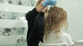 Colorist van de vrouwenkapper thuis in de badkamers zet verf op het haar van een jonge vrouw, toepast verf met een borstel stock footage