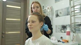 Colorist van de vrouwenkapper thuis in de badkamers zet verf op het haar van een jonge vrouw, toepast verf met een borstel stock video