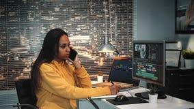 Coloriste de métis parlant par le smartphone et écrivant des notes dans le studio moderne de production banque de vidéos