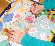 Coloritura del bambino dentro su una tavola dello scrittorio Fotografia Stock