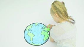 Coloritura della ragazza in una mappa del mondo stock footage