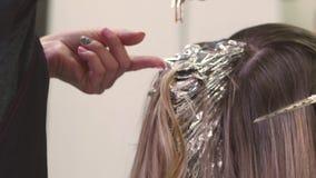Coloritura di capelli Il parrucchiere Dye la ragazza bionda che si siede in un salone di bellezza, Barber Brush Hair Holds Paint  video d archivio