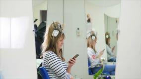 Coloritura di capelli Il parrucchiere Paint per i capelli è una ragazza bionda simpotic, sedentesi in un salone di bellezza, un p stock footage