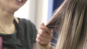 Coloritura di capelli Il parrucchiere Paint per la bella bionda dei capelli che si siede in un salone di bellezza, parrucchiere p archivi video