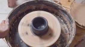 Coloritura di un vaso su una ruota delle terraglie stock footage