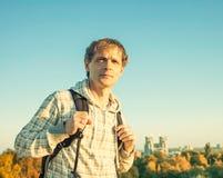 拿着背包和看日落的风格化colorized葡萄酒愉快的人画象 免版税图库摄影