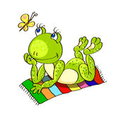Colorless background with a green frog lies on the colored beach Royalty Free Stock Photos