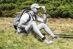 Colorless man Traveler sits on the grass and puts his hand to the cap visor. Ukraine, Carpathians, Dragobrat Stock Photography