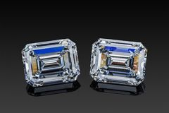 Colorless transparent sparkling set of two luxury gemstones square shape emerald cut diamonds isolated on black background stock image