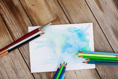 Colorpencils and brush on table. Colored pencils and brush lies on table. Green and blue colors Stock Image