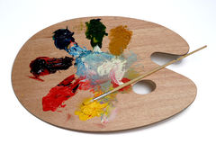 Colors. Artist pallet smeared with colorful paints plus brush Royalty Free Stock Photography