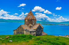 The colors of Armenia. The Surp Arakelots (Holy Apostles) Church of Sevanavank Monastery with the Sevan Lake and snowy mountains on the background, Sevan Royalty Free Stock Photography