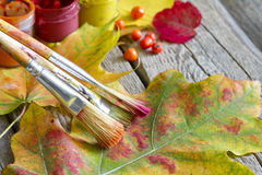 Colors of autumn abstract with paint brush and leaves Stock Images