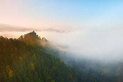 Colors of autumn romantic morning. Wooden house or hut for hiker on the green  peak of forest hill. Autumn mist bellow in valley. Stock Image