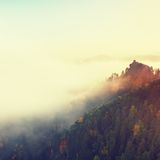 Colors of autumn romantic morning. Wooden house or hut for hiker on the green  peak of forest hill. Autumn mist bellow in valley. Royalty Free Stock Images