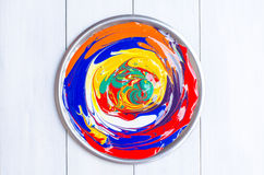 Colors background. Mixed acrylic colors in stainless plate on white wooden Royalty Free Stock Images