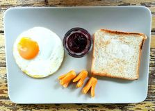 The colors of  breakfast. The nice breakfast fried egg fried sausage fruit jam and bread Stock Image
