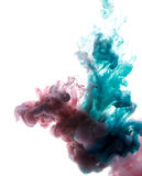 Colors dropped into liquid and photographed while in motion. Cloud of silky ink in water on white isolated royalty free stock image