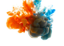 Colors dropped into liquid and photographed while in motion. Ink shape or swirling in water for design or decorate background or a Stock Photos