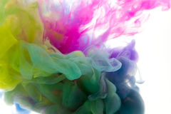 Colors dropped into liquid and photographed while in motion. Ink shape or swirling in water for design or decorate background or a Stock Images