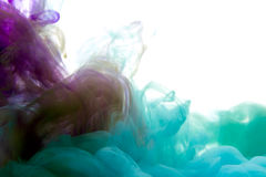 Colors dropped into liquid and photographed while in motion. Ink Stock Photo