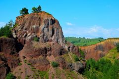 The colors of extinct vulcano of Racos Brasov, Romania, Heghes Peak. Volcanic rock Transylvania Ardeal cliff stone sky mining exploitation canyon beautiful royalty free stock images