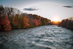 COLORS OF FALL OVER A RAGING RIVER stock image