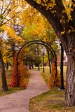 Garden Arch in Autumn. The colors of fall are surrounding this archway in the park in autumn Royalty Free Stock Photo
