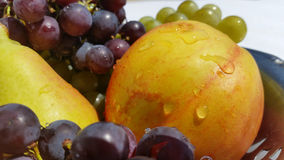 Colors and fruit flavors. Fruit basket consisting of grapes, peaches and pears Stock Images