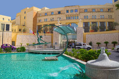 Colors of Hilton Malta Hotel. Buildings of luxury Hilton Malta Hotel with fountain in front of entrance. Simple fountain is decorated by elegant figure of Royalty Free Stock Images