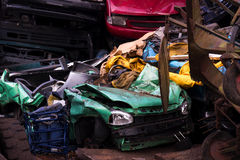 Colors on the junkyard, crushed turquoise scrap car, yellow garb Stock Image