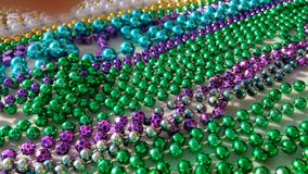 Colorful Beads for Mardi Gras days. Green, blue, purple, silver, gold and white metal beads. Carnival colors in rows showing the strands and colors of the royalty free stock images