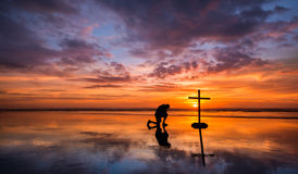 Colors of Prayer. Wonderful reflection on a beach at sunset, with a man kneeling by it Stock Image