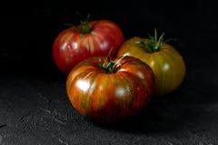 colors röd tomatyellow för heirloom Tre tomater av olika färger på en svart texturerad bakgrund royaltyfri bild