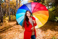 Colors of rainbow on umbrella. A portrait of a beautiful young woman in an autumn forest with bright and colorful umbrella. Lifestyle, autumn fashion, beauty royalty free stock image