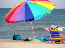 Colors On The Sand. Colorful umbrella and chair with a woman enjoying the last warm days of summer Stock Image