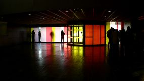 Colors and silhouettes in the darkness. Backlit from the inside of Rio Hortega hospital's lobby in Valladolid with silhouettes of people contrasting over the royalty free stock image