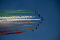 Colors in the sky. A team of 9 planes flying together on air show leaving colors behind Royalty Free Stock Photos