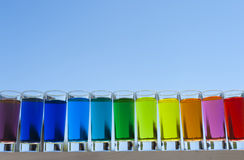 Colors in the Sky - Color Water in shot glasses with the sun shining through Royalty Free Stock Photography