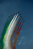 Mixed colors team work. Team of 9 planes flying together on air show leaving colors behind stock photography
