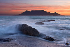 The colors of Table Mountain. At sunset with large rock in foreground Stock Images