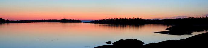 Colors of white night. Pink dawn in the blue sky reflected in quiet water. The white nights on Kem skerry, White sea stock photography