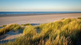 The sun is setting on the beach of Schiermonnikoog Friesland, Netherlands. The colortones are becoming warmer when the evening has arrived on the shore of the Royalty Free Stock Photography