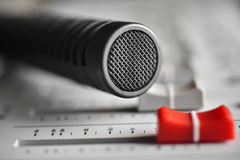 Colose up of a hi-fi condenser microphone wtih red slide level. Over a digital sound recorder Royalty Free Stock Image
