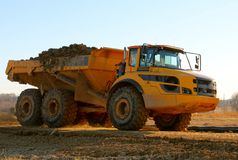 Colossal Dump Truck with a full load of Dirt. A Huge Construction Equipment Dump Truck carries freshly dug dirt stock photos