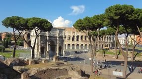 Colosseo and Constantine Arch in Rome. Piazza del Colosseo in Rome with the Arc of Constantine, people and trees Stock Photo