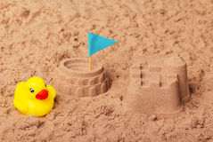 Colosseum and castle, flag, rubber duck in sand. Background. stock image